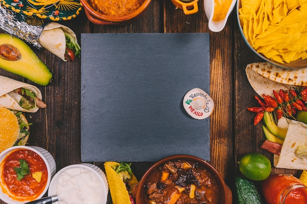 Black slate surrounded by variety of delicious mexican food on brown table Free Photo