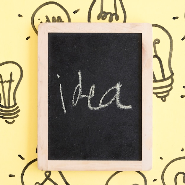 Black slate with idea word surrounded by light bulbs on yellow backdrop Free Photo