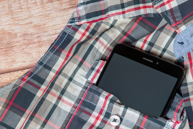 Black smartphone sticking out of a sleeveless shirt pocket Premium Photo