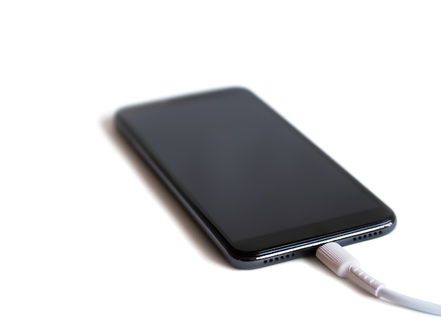 白い背景、モックアップ、コピースペースでバッテリーを充電するための接続ケーブル付きの黒いスマートフォン Premium写真