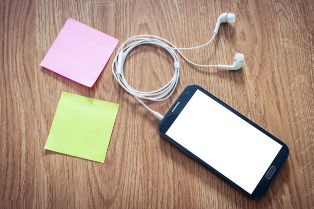 Black smartphone with white screen with headphones, sticky notes on wooden surface Premium Photo