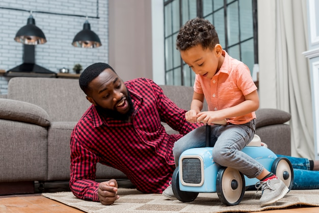 Black son driving toy car with father Free Photo