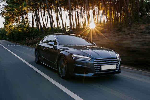 Black sport car highway drive in the sunset. Free Photo