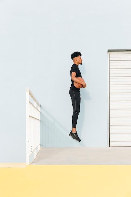 黒のスポーツマンがポーチでバスケットボールでジャンプ 無料写真