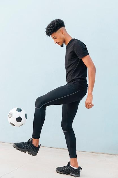 Black sportsman kicking football at blue wall background Free Photo