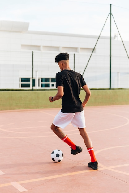 Black sportsman playing with football at sports ground Free Photo