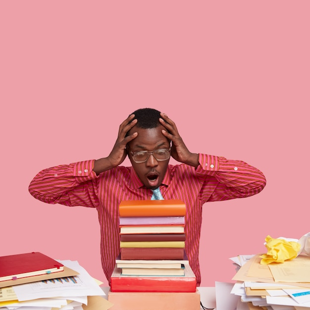 Black stupefied young teacher keeps hands on head, opens mouth widely, stares at pile of books, prepares lecture for students Free Photo