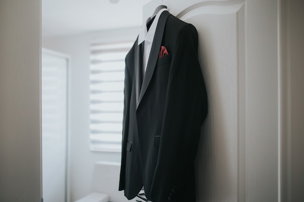 黒のスーツと白いシャツがドアからハンガーにぶら下がっています 無料写真
