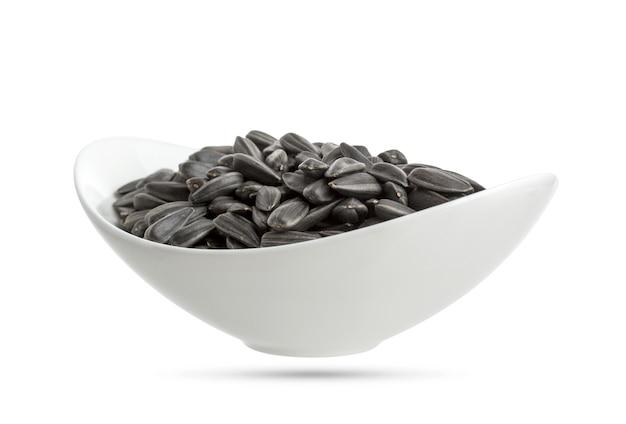 ボウルに白で隔離される黒いヒマワリの種 Premium写真
