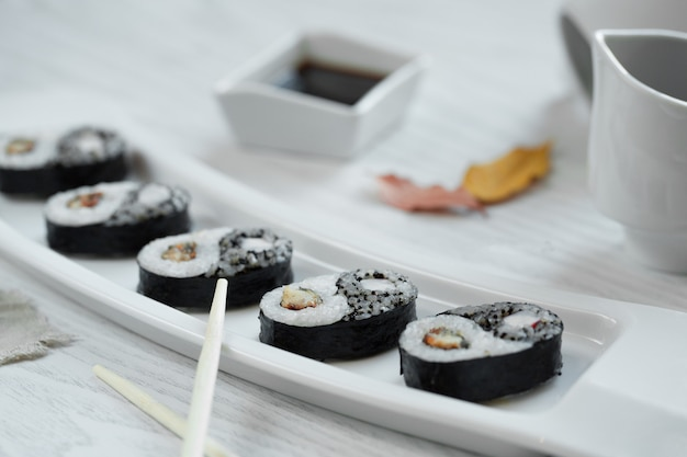 Black sushi with sauce in the plate Free Photo
