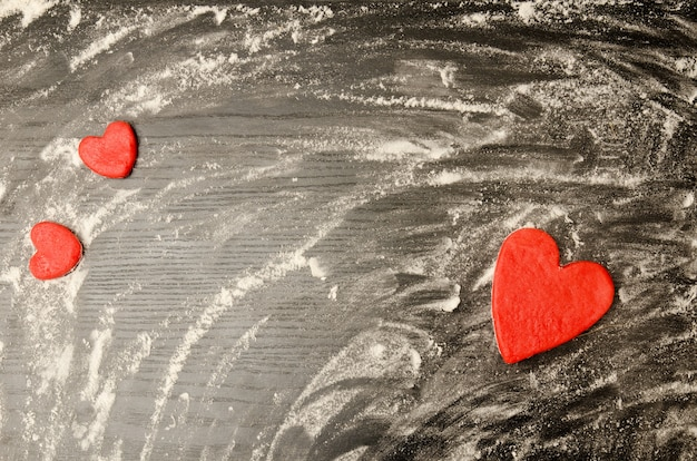 Black table of scattered flour. red hearts of dough on the corners of the frame, Premium Photo