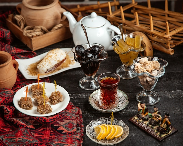 Black tea in armudu glass with various sweets Free Photo