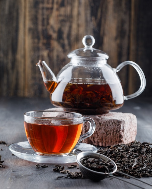 Black tea in teapot and cup with dry tea, brick side view on a wooden surface Free Photo