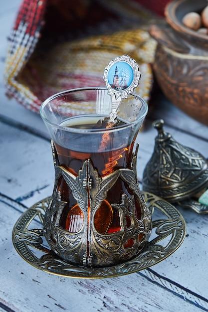 Tè nero in una tazza di vetro tradizionale e biscotti sulla tavola di legno blu Foto Gratuite