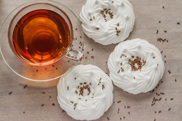 Black tea in transparent cup an air homemade meringues close up Premium Photo