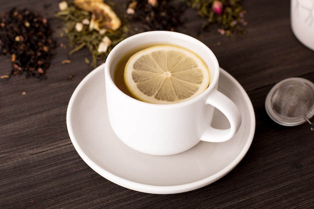 Black tea with lemon and several views of tea on a wooden table Premium Photo