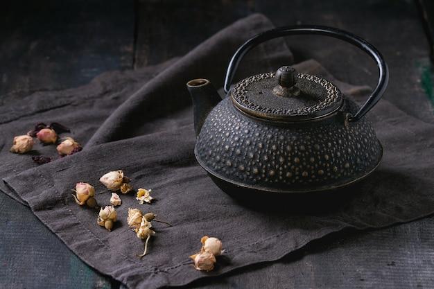 Black teapot with dry roses Premium Photo