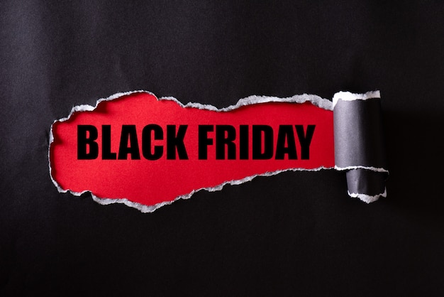 Black torn paper and the text black friday on red Premium Photo