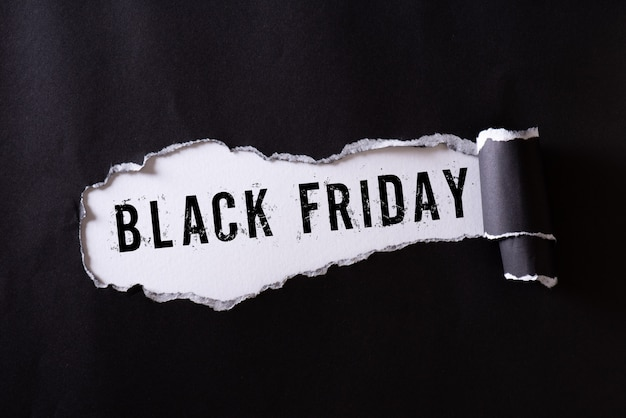 Black torn paper and the text black friday on white. Premium Photo