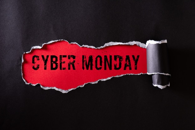 Black torn paper and the text cyber monday on red Premium Photo