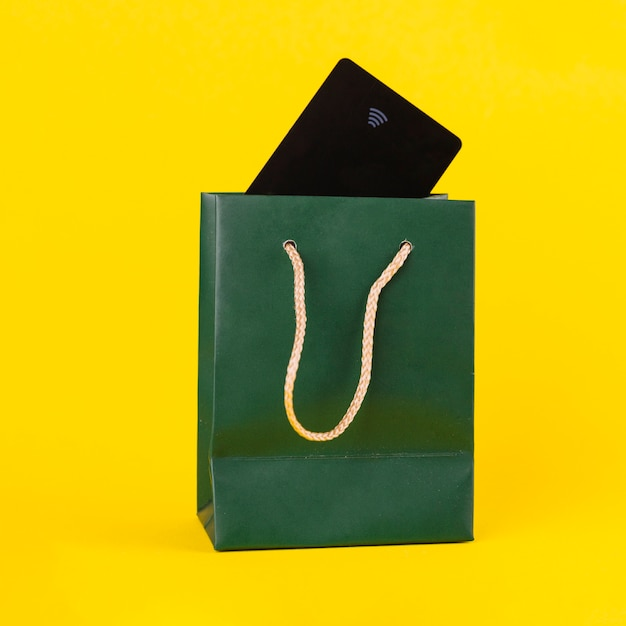 Black travelling card inside the green paper shopping bag against yellow background Free Photo