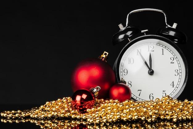 Black vintage alarm clock with christmas baubles and decor on dark black background Premium Photo
