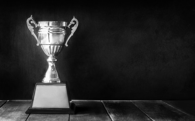 Black and white champion trophy on wood table with blackboard copy space Premium Photo