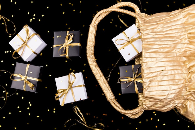 Black and white gift boxes with gold ribbon pop out from golden bag on shine surface, Premium Photo