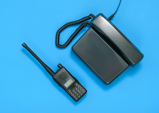 Black and white image of a walkie-talkie and telephone on a blue background. Premium Photo