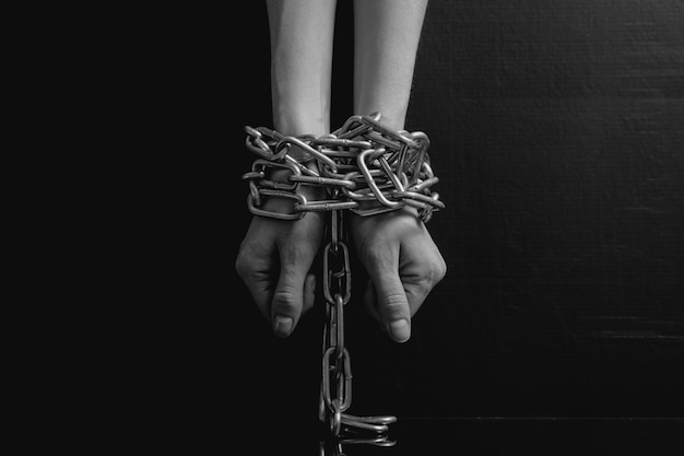 Black and white minimalistic women hands chained close-up Premium Photo
