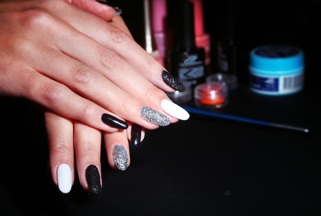 Black, white nail art manicure. holiday style bright manicure with sparkles. beauty hands. stylish nails, nail polish Premium Photo