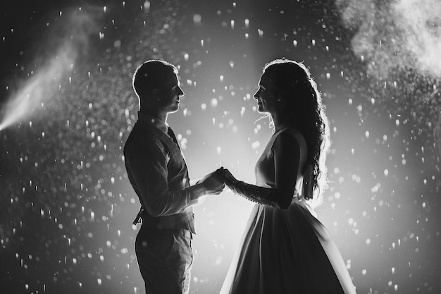 Black and white photo of cheerful bride and groom holding hands and smiling at each other against glowing fireworks Free Photo