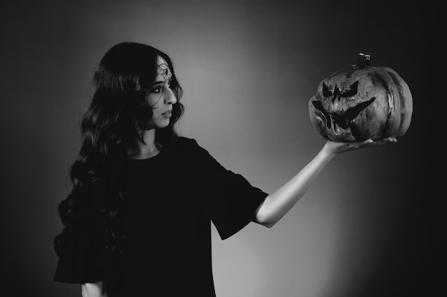 Black and white photo of girl looking at pumpkin Free Photo