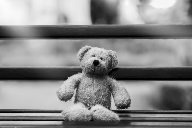 Black and white photo of teddy bear with sad face sitting on wooden beance , lonely teddy bear sitting alone outside in gloomy day, lonely concept, international missing children's day. Premium Photo