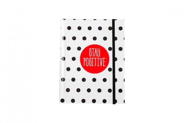Black and white polka dot note book with red circla and stay positive inscription on the cover. Premium Photo