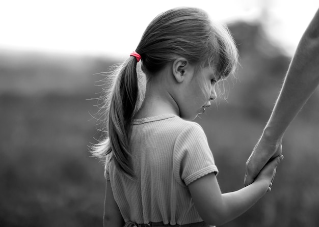 Black and white portrait of little girl holding a hand of her mother Premium Photo