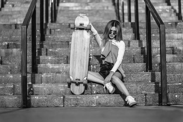스케이트 보드에 앉아 젊은 여자의 흑백 초상화. 고품질 사진 프리미엄 사진