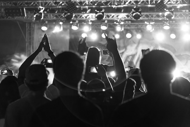 Black and white silhouette of people in crowd at a music festival. concert with backlit standing dancing people Premium Photo