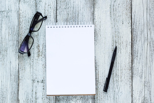 Black and white still life: opened blank notepad, notebooks, pen, glasses. Premium Photo