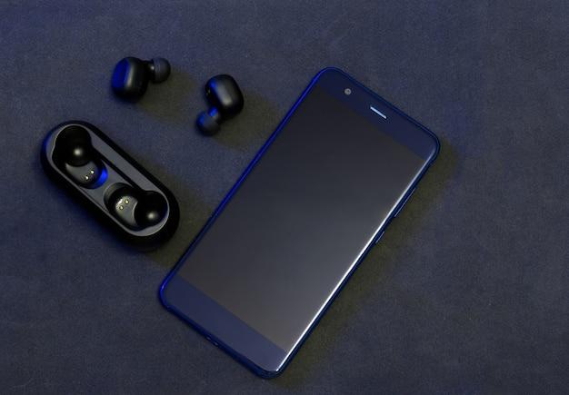 Black wireless headphones with blue cellphone on dark background. Premium Photo