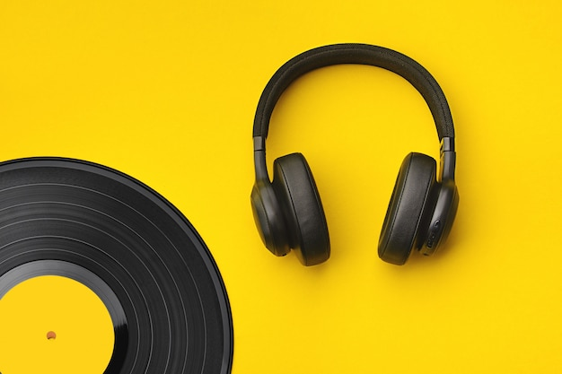 Black wireless headphones with vinyl record. music concept. Premium Photo