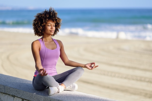 black woman afro hairstyle in lotus asana with eyes closed in the