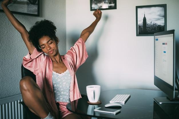 朝はコンピューターとコーヒーでストレッチ黒人女性自宅 Premium写真