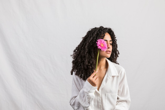 Black woman holding gerbera at face Free Photo