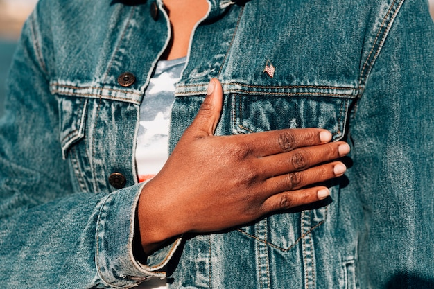 Black woman holding hand on heart Free Photo