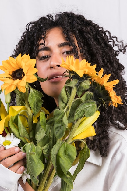 Black woman holding yellow flowers at face Free Photo