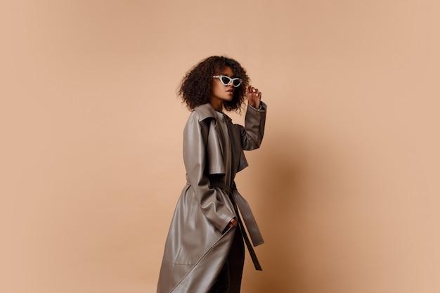 スタジオでベージュ色の背景にポーズトレンディなグレーレザージャケットの黒人女性。冬と秋のファッションを見てください。 無料写真