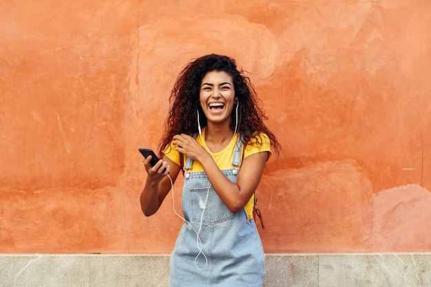 Black woman laughing and listening to music with earphones. Premium Photo