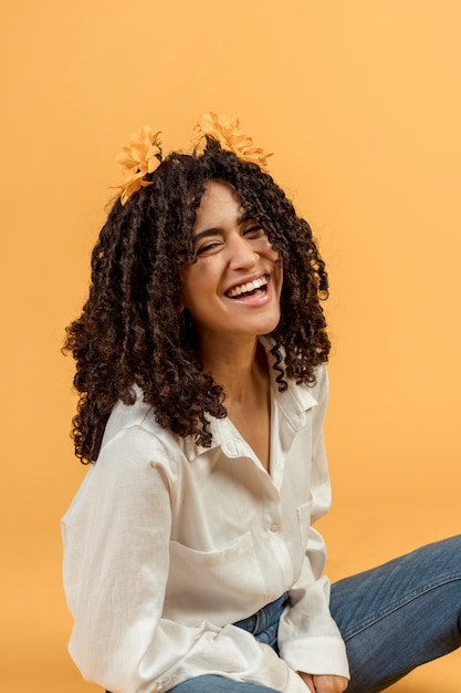 Black woman with flowers in hair laughing Free Photo