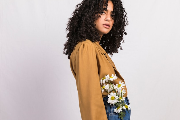 Black woman with flowers in jeans pocket Free Photo